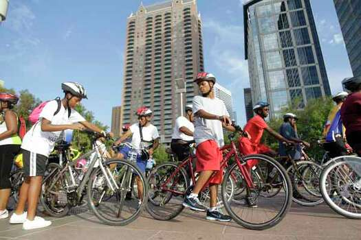 Kai Williams, 13, left, with his grandmother, Diana McPherson, and friend, Tyler Lattimore, right, all of Gainesville, Fla., prepare to start  the bike ride Saturday at Discovery Green. Photo: Melissa Phillip, . / © 2012 Houston Chronicle