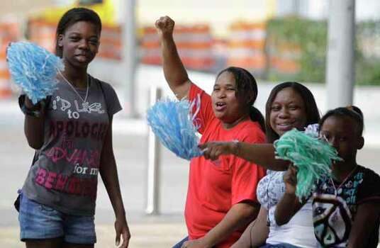 Alisha Jordan, 13, left, Dawna Minor, Hatta Hogan and LaDeisha Hogan, 10, cheer for the riders. Photo: Melissa Phillip, . / © 2012 Houston Chronicle