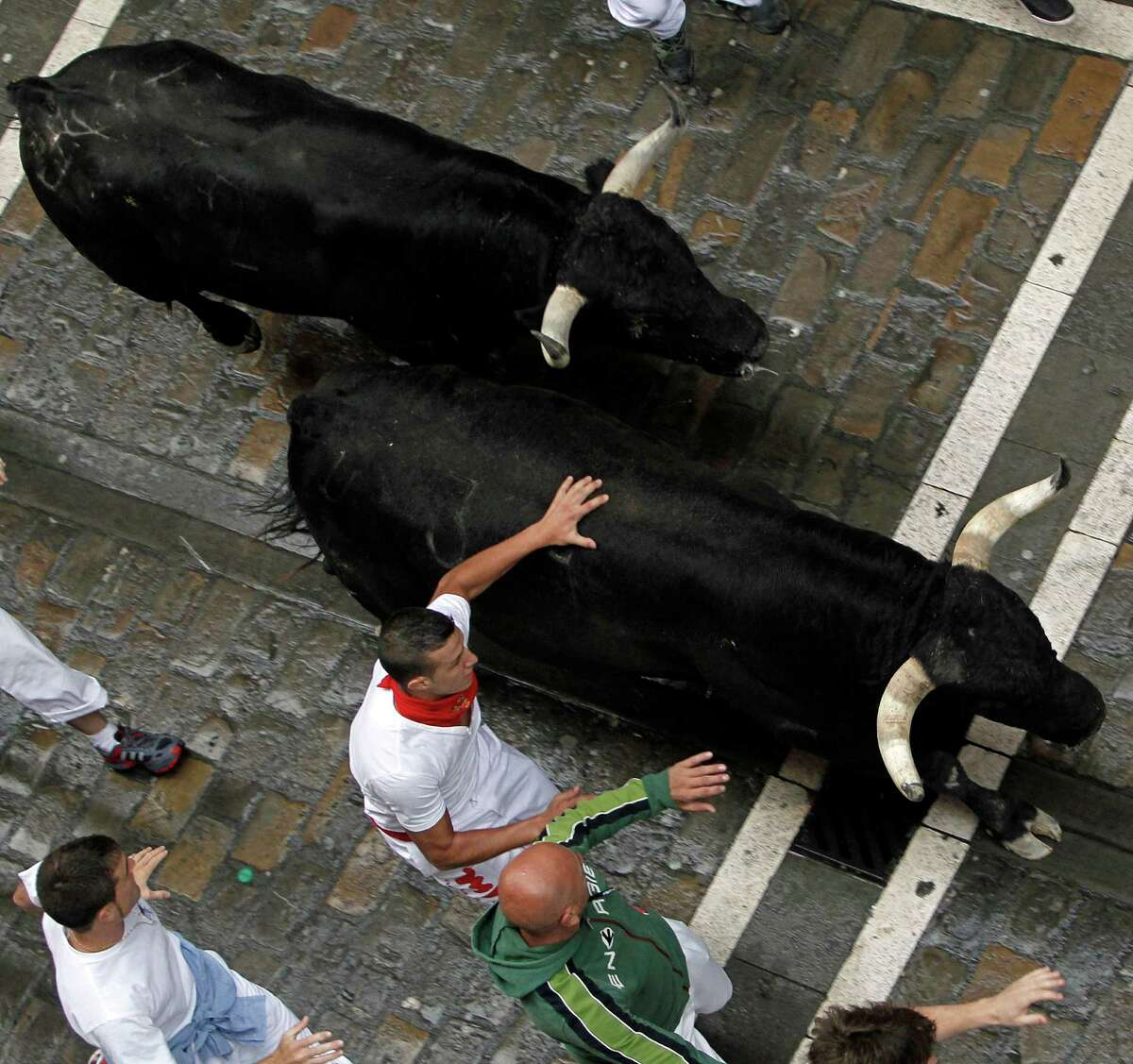 Revelers run with Dolores Aguirre Yabarra ranch fighting bulls during the running of the bulls of the San Fermin festival, in Pamplona, Spain, Saturday, July 7, 2012. The San Fermin running of the bulls festival became world famous with the publication of Ernest Hemingway's 1926 novel