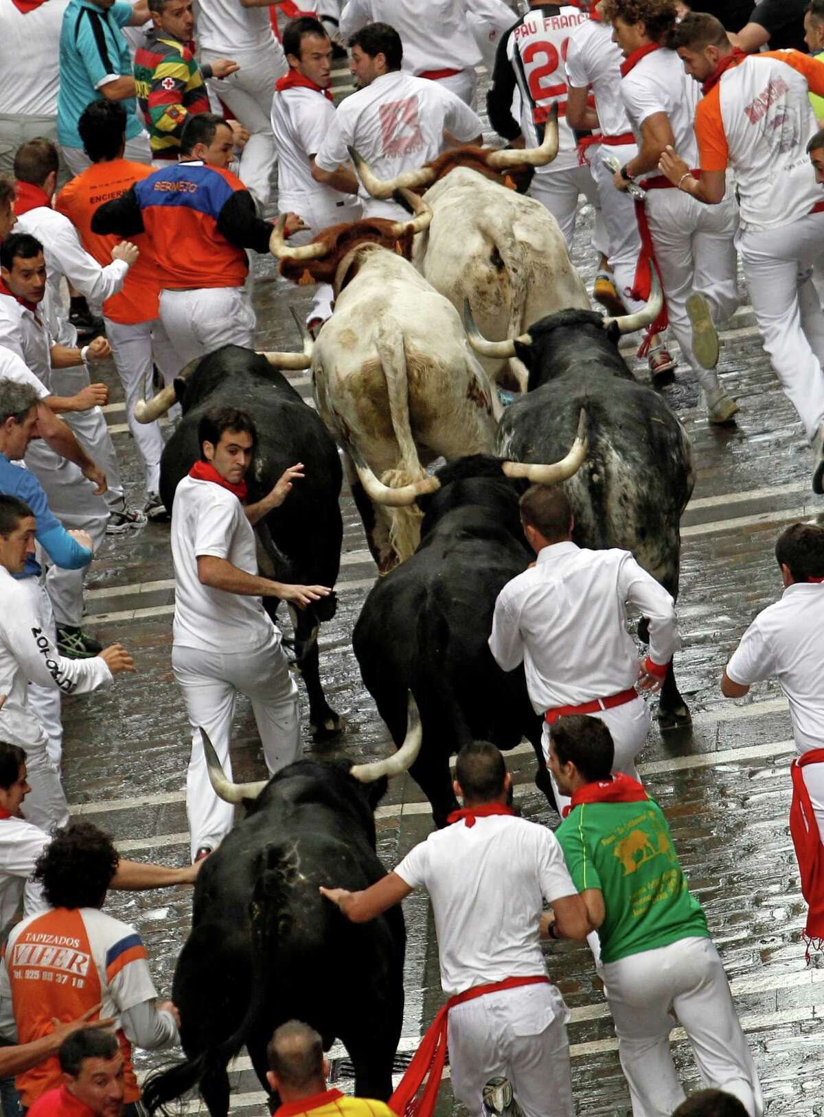 Revelers run with Dolores Aguirre Yabarra ranch fighting bulls.