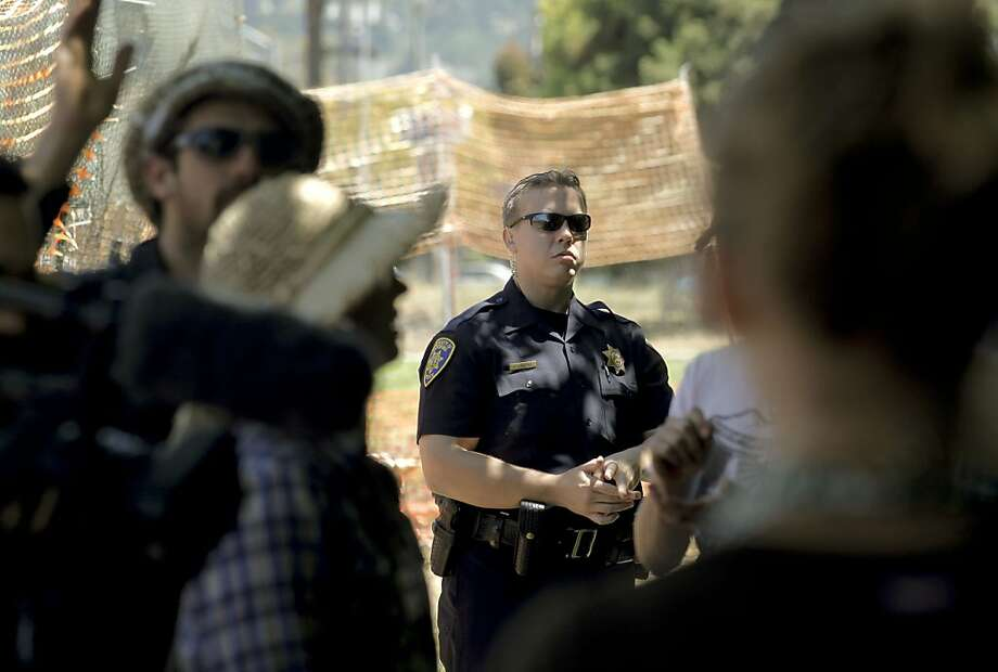 One member of the University of California Police keeps a watch on the gathering after the harvest. Members of Occupy the Farm in Berkeley returned to the Gill Agricultural Tract, on Saturday July 7, 2012, in Berkeley, Calif., to harvest the vegetables that they planted months before, to now distribute them to members of the local community. The plot of agricultural land on San Pablo Ave. is operated by UC Berkeley. Photo: Michael Macor, The Chronicle