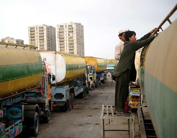 Pakistani drivers clean a fuel tanker truck, used to transport fuel to NATO forces in Afghanistan, parked along a road in Pakistan's port city of Karachi on July 7, 2012.  Islamabad reopened overland routes to NATO convoys earlier this week after closing them in protest at a US air raid that killed 24 Pakistani soldiers at a border post in November.  AFP PHOTO/Asif HASSANASIF HASSAN/AFP/GettyImages Photo: Asif Hassan, AFP/Getty Images