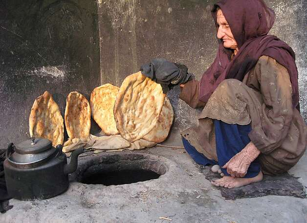 An Afghan elderly woman bakes bread at her home in Jalalabad on July 7, 2012.  Poverty and an ongoing insurgency by the ousted Taliban still pose a threat to the stability of the country.  AFP PHOTO/Noorullah ShirzadaNoorullah Shirzada/AFP/GettyImages Photo: Noorullah Shirzada, AFP/Getty Images