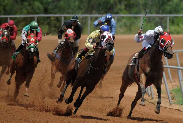 Riders and quarter horses run around the turn at the Gillespie County Fairgrounds in Fredericksburg on Saturday, July 7, 2012. Photo: Billy Calzada, San Antonio Express-News / © 2012 San Antonio Express-News