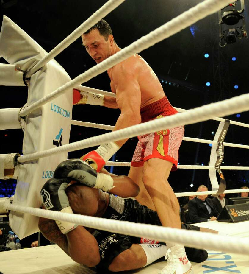 Wladimir Klitschko of Ukraine stands over Tony Thompson of the United States after one of his two knockdowns Saturday in Bern, Switzerland. Photo: Daniel Maurer, Associated Press