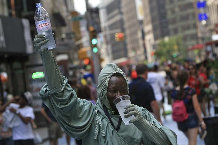 A street performer who makes tips by posing as the Statue of Liberty with tourists takes a water break while working in Times Square, Saturday, July 7, 2012, in New York.  A heat warning is in effect though the evening in New York metropolitan area, and a severe thunderstorm watch has also been issued. (AP Photo/Mary Altaffer) Photo: Mary Altaffer, Associated Press