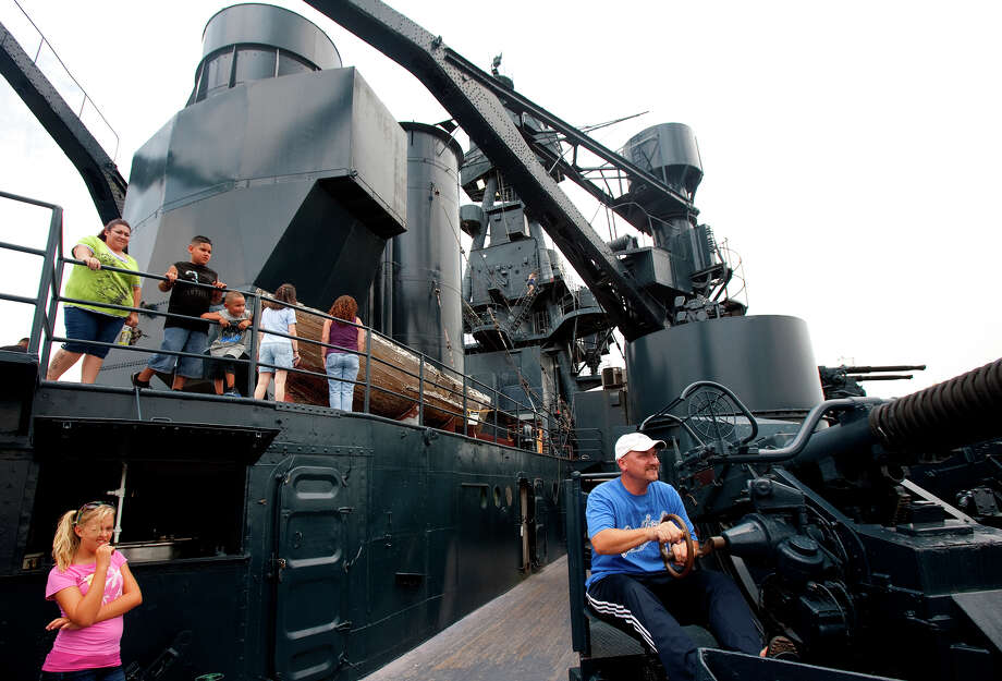 Mackenzie Erdley, 12, left, watches as her father, Steve Erdley, right, operates a 40mm Bofors antiaircraft gun atop the Battleship Texas Saturday, July 7, 2012, in La Porte. The state historic site reopened to the public Saturday after being closed since June 24 for repairs to fix leaks in the vessel's metal hull. Photo: Cody Duty, Houston Chronicle / © 2011 Houston Chronicle