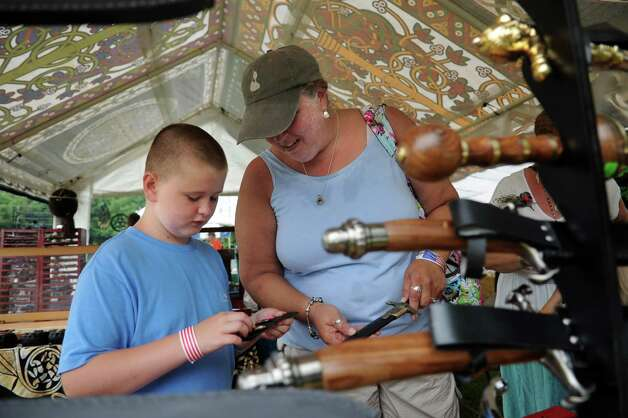 Linda Fitzpatrick and her son, Daniel, 10, of Darien, look at swords and knives at La Wren's Nest's tent during the Round Hill Highland Games at Cranbury Park in Norwalk on Saturday, July 7, 2012. Photo: Lindsay Niegelberg / Stamford Advocate