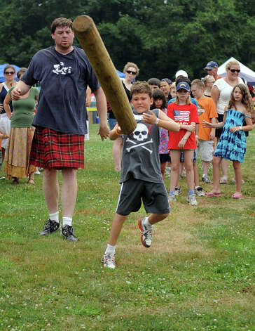 Blake Wallace, 9, participates in the children's Caber Toss during the Round Hill Highland Games at Cranbury Park in Norwalk on Saturday, July 7, 2012. Photo: Lindsay Niegelberg / Stamford Advocate