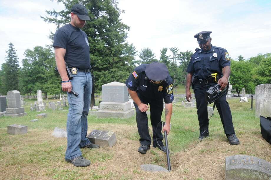 Hudson police probe a cemetery for a woodchuck believed to have stolen flags at gravestones. (Lance Wheeler / Special to the Times Union)