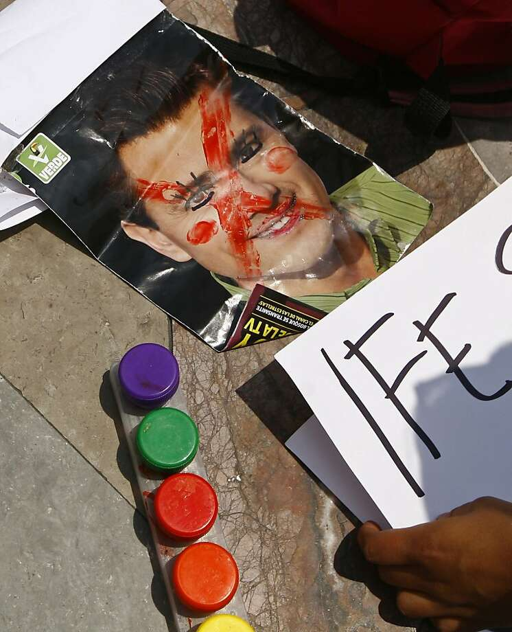 A defaced image of Enrique Pena Nieto lies on the floor as demostrators prepare for a march, in Mexico City, Saturday, July 7, 2012. Tens of thousands marched in rejection of the final count in the presidential election showing former ruling party candidate Enrique Pena Nieto as the victor. They believe the PRI engaged in vote-buying that illegally tilted millions of votes. PRI officials deny the charge. (AP Photo/Marco Ugarte) Photo: Marco Ugarte, Associated Press
