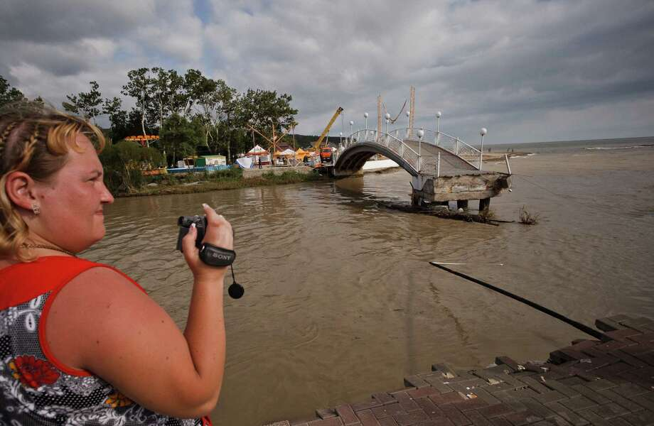 A woman takes video of the flood in the Black Sea resort of Gelendzhik, southern Russia, Saturday, July 7, 2012. Intense flooding in the Black Sea region of southern Russia killed 103 people after torrential rains dropped nearly a foot of water, forcing many to scramble out of their beds for refuge in trees and on roofs, officials said Saturday. (AP Photo/Ignat Kozlov) Photo: Ignat Kozlov