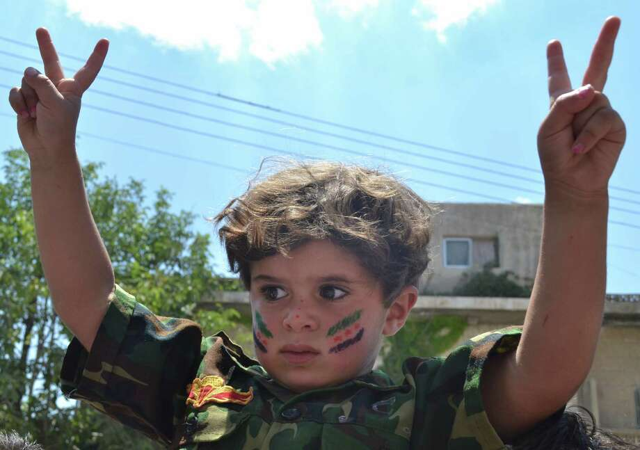 This citizen journalism image released by Shaam News Network taken Friday, July 6, 2012 purports to show a child in a military  uniform and flashing the victory sign at an anti-Assad protest in Kafr Nabil, in Northwestern Syria. (AP Photo/Ra'ed Alfares, Shaam News Network) THE ASSOCIATED PRESS IS UNABLE TO INDEPENDENTLY VERIFY THE AUTHENTICITY, CONTENT, LOCATION OR DATE OF THIS CITIZEN JOURNALISM IMAGE Photo: Ra'ed Alfares