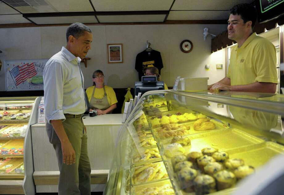 President Barack Obama looks over the selection as he stops to get a pie and cookies at Kretchmar's bakery in Beaver, Pa., Friday, July 6, 2012. Obama is on a two-day bus trip through Ohio and Pennsylvania. (AP Photo/Susan Walsh) Photo: Susan Walsh