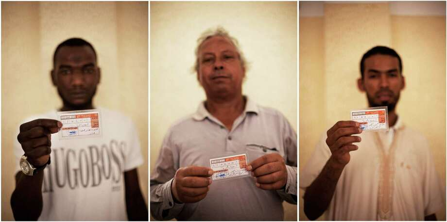 This combo image of three photographs shows Libyan men holding their elections ID at a polling station in Tripoli, Libya, Saturday, July 7, 2012. Jubilant Libyan voters marked a major step toward democracy after decades of erratic one-man rule, casting their ballots Saturday in the first parliamentary election after last year's overthrow and killing of longtime leader Moammar Gadhafi. But the joy was tempered by boycott calls, the burning of ballots and other violence in the country's restive east. (AP Photo/Manu Brabo) Photo: Manu Brabo