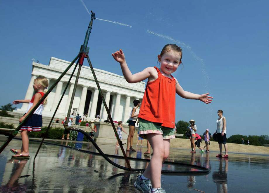 Sophie, 3, from Connecticut, frolics with a water sprinkler set up at the National Mall near the Lincoln Memorial, rear, in Washington Saturday, July 7, 2012.  The heat gripping much of the country is set to peak Saturday in many places, including some Northeast cities, where temperatures close to or surpassing 100 degrees are expected. (AP Photo/Manuel Balce Ceneta) Photo: Manuel Balce Ceneta