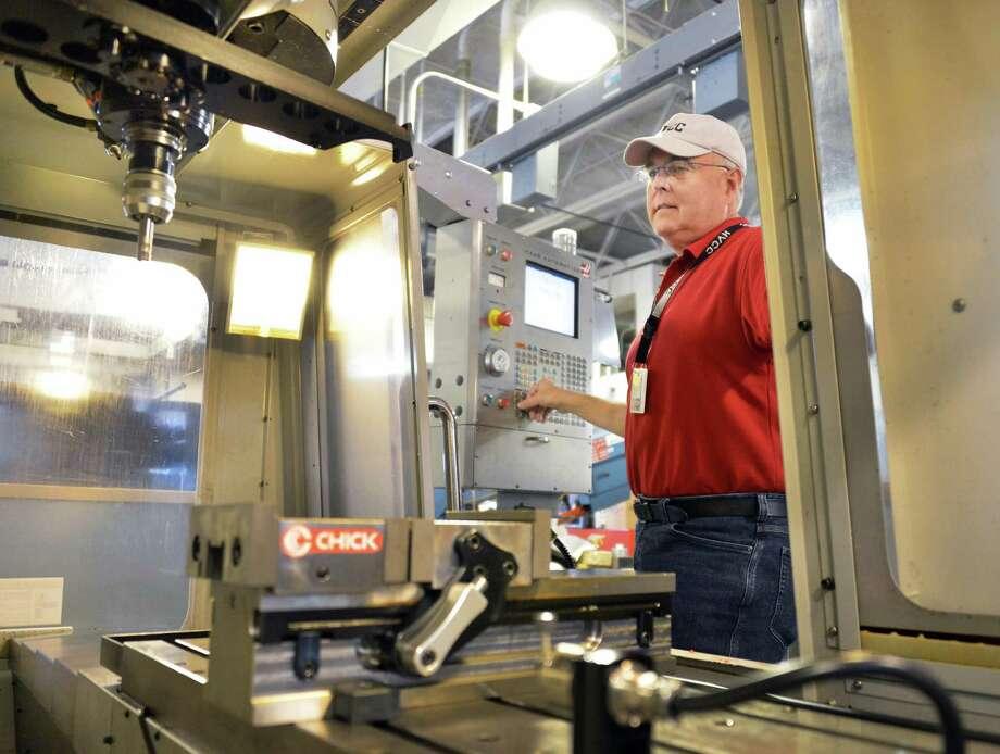 HVCC professor David Larkin programs a HAAS VF 2 machining center in the school's Manufacturing Technical Systems lab Thursday July 5, 2012.  (John Carl D'Annibale / Times Union) Photo: John Carl D'Annibale / 00018345A