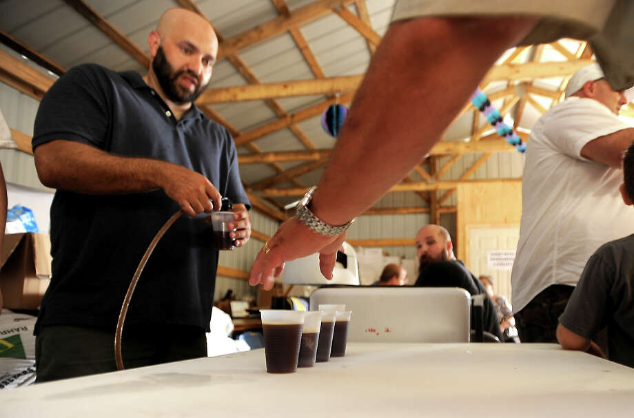 Aaron Bossley pours samples of beer during the Texas Big Beer Brewery opening party in Buna, Saturday, July 7, 2012.Tammy McKinley/The Enterprise Photo: TAMMY MCKINLEY