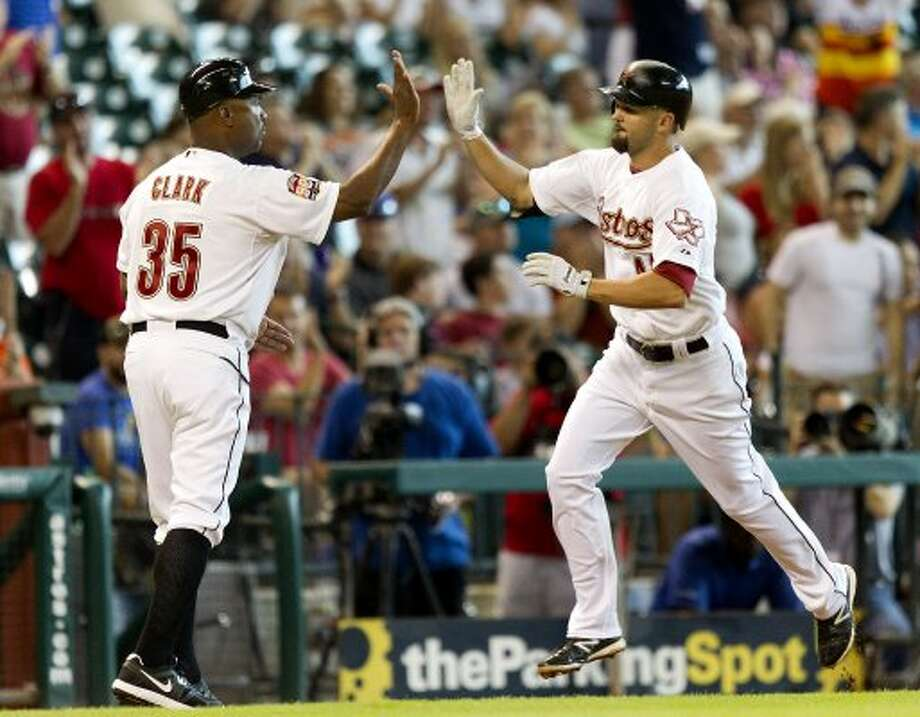 Scott Moore receives a high five from Dave Clark after hitting a home run in the third inning. (Bob Levey / Getty Images)
