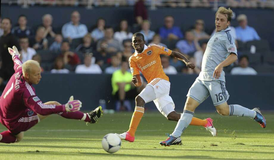 Boniek Garcia takes a shot past Seth Sinovic while Jimmy Nielsen blocks the ball. Photo: Ed Zurga, Getty Images / 2012 Getty Images