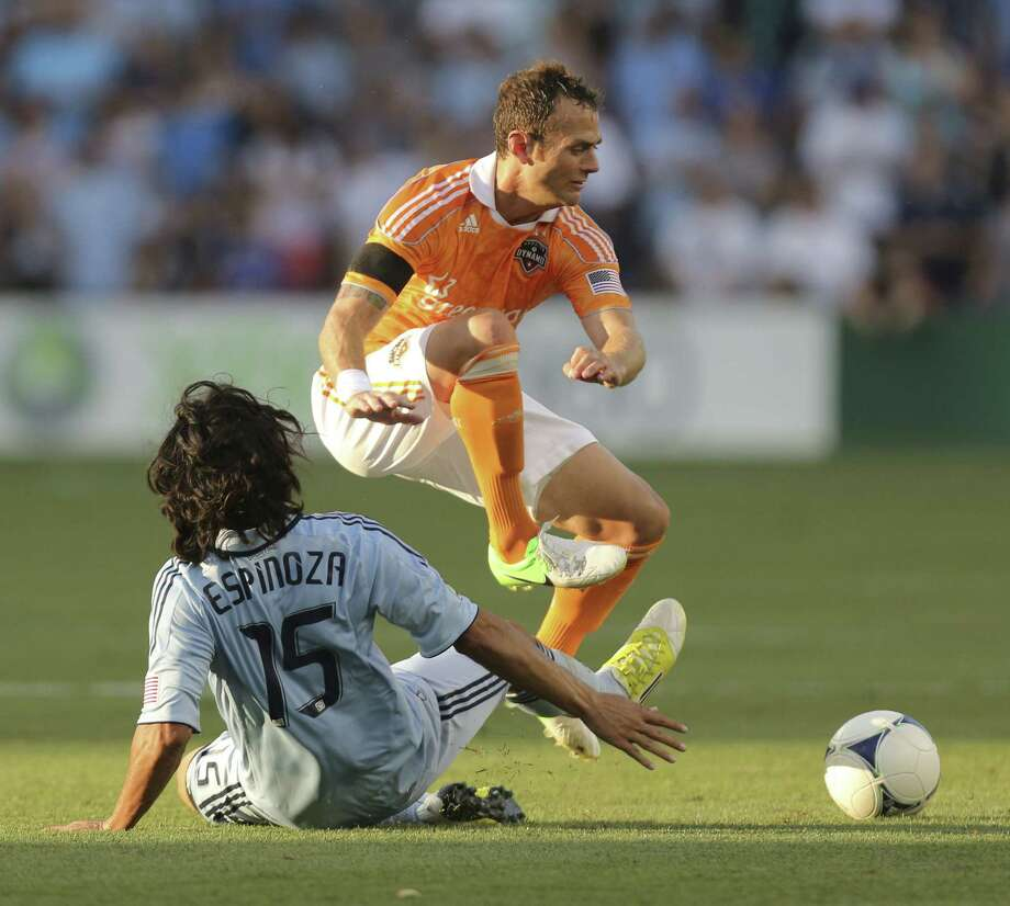 Roger Espinoza clears the ball away from Brad Davis.  Photo: Ed Zurga, Getty Images / 2012 Getty Images