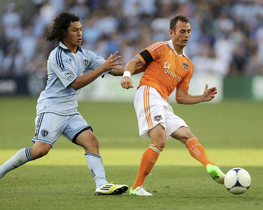 Brad Davis passes the ball against Roger Espinoza in the first half.  Photo: Ed Zurga, Getty Images / 2012 Getty Images