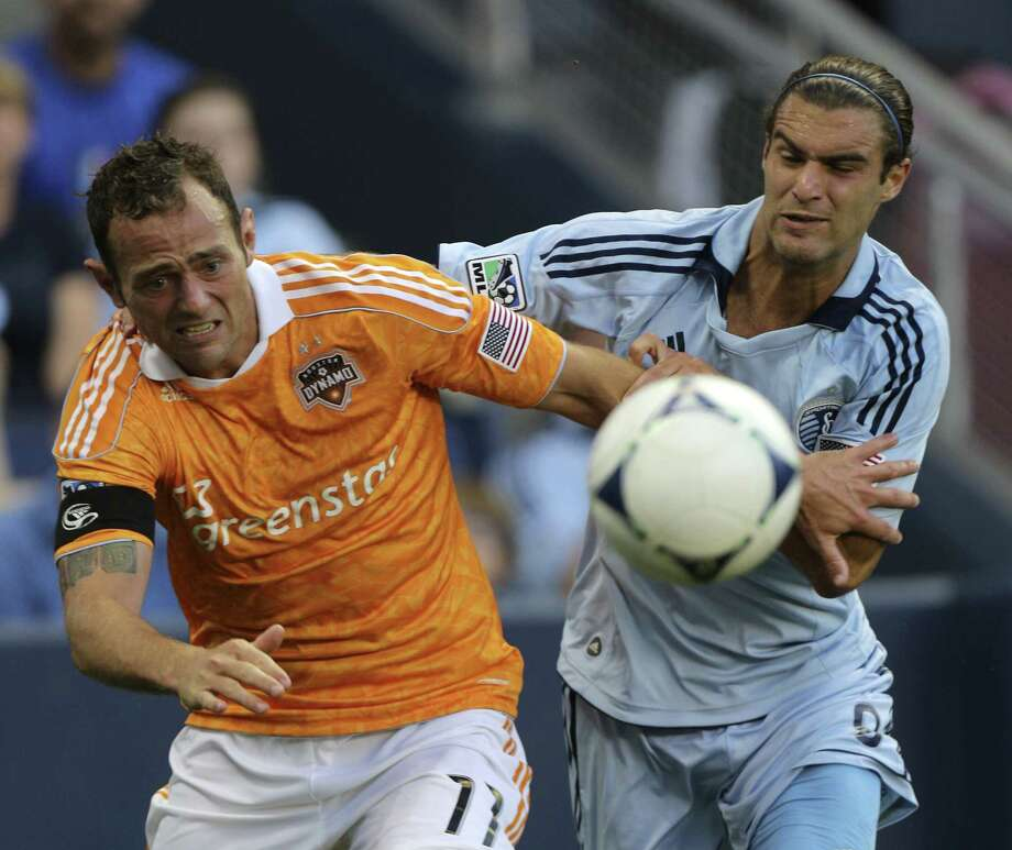 Brad Davis and Graham Zusi chase down a loose ball in the second half. Photo: Ed Zurga, Getty Images / 2012 Getty Images