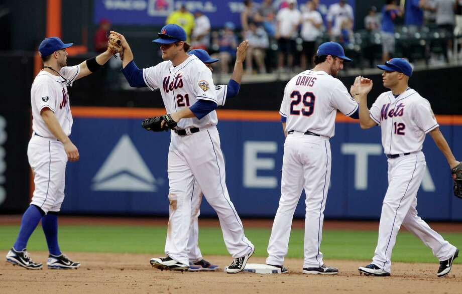 New York Mets' David Wright, left, celebrates with teammates Lucas Duda (21), Ike Davis and Scott Hairston (12) after a baseball game against the Chicago Cubs, Saturday, July 7, 2012, in New York. The Mets won the game 3-1. (AP Photo/Frank Franklin II) Photo: Frank Franklin II
