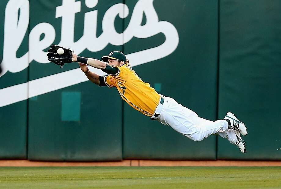 OAKLAND, CA - JULY 07:  Josh Reddick #16 of the Oakland Athletics dives to catch a ball hit by Ichiro Suzuki #51 of the Seattle Mariners in the third inning at O.co Coliseum on July 7, 2012 in Oakland, California.  (Photo by Ezra Shaw/Getty Images) Photo: Ezra Shaw, Getty Images