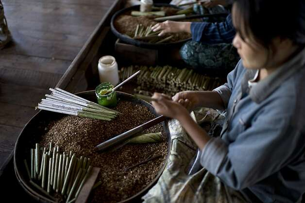 A woman makes traditional cheeroot cigars in a workshop on Inle Lake in Myanmar's Shan state on December 30, 2010. The 13.5-mile-long and seven-mile wide lake is one of the top tourist destinations in the country that was formerly called Burma. The waters are dotted with stilted villages and floating gardens of the Intha tribe and boats are the main mode of transportation. AFP PHOTO / VOISHMEL (Photo credit should read VOISHMEL/AFP/Getty Images) Photo: Voishmel, AFP/Getty Images