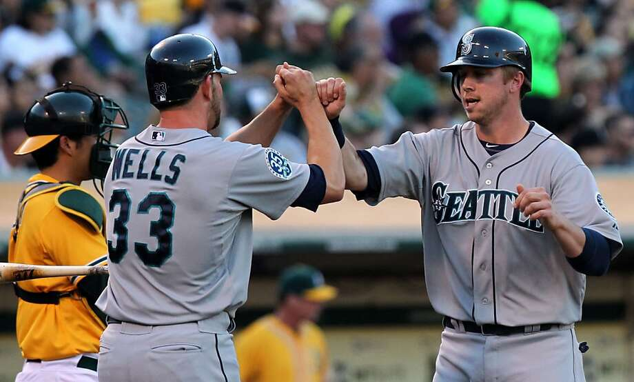 Seattle Mariners Casper Wells greets Justin Smoak at home plate after they scored off a hit by Brendan Ryan in the second inning of their MLB baseball game against the  Oakland Athletics Saturday, July 7, 2012, in Oakland California. Photo: Lance Iversen, The Chronicle