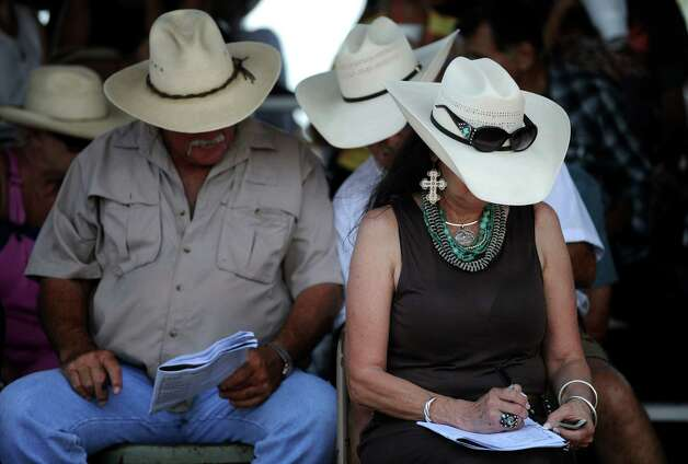 People at the Gillespie County Fairgrounds look over their programs between horse races in Fredericksburg on Saturday, July 7, 2012. Photo: Billy Calzada, San Antonio Express-News / © 2012 San Antonio Express-News