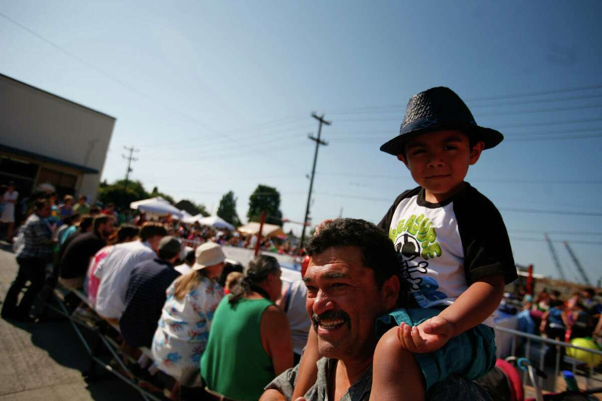 A boy sits on his father's shoulders.