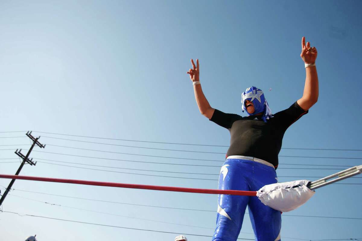 A wrestler greets the crowd during the second annual Lucha Libre en la Calle event held in South Park in Seattle on Saturday, July 7, 2012. Lucha Libre is a form of wrestling that originates from Mexico in which wrestlers wear colorful masks.