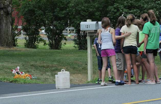 Family and friends of Kari Liedel gather around a roadside memorial on West Milton Road the day after Liedel was struck and killed. The driver was charged with DWI. (Paul Buckowski/Times Union)