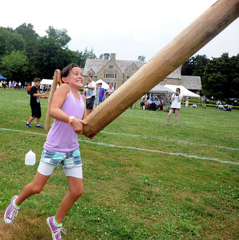 Isabella Fragomeli, 10, of Pleasanton, Calif., participates in the children's Caber Toss during the Round Hill Highland Games at Cranbury Park in Norwalk on Saturday, July 7, 2012. Photo: Lindsay Niegelberg / Stamford Advocate