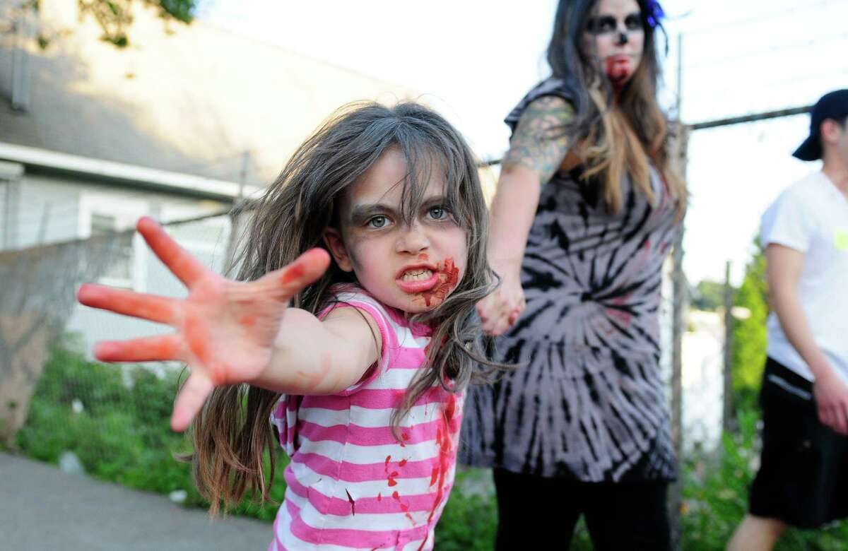 A young girl gives her best zombie face.