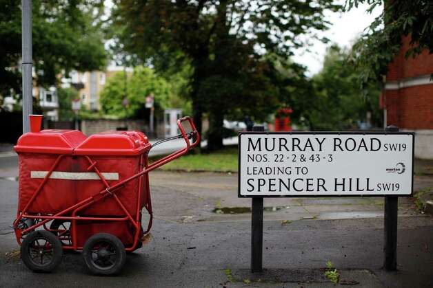 A Royal Mail caddy is parked next to a road sign in Wimbledon village, England, Sunday, July 8, 2012. Andy Murray of Britain will face Roger Federer of Switzerland in a men's singles final match at the All England Lawn Tennis Championships on Sunday afternoon. Photo: Anja Niedringhaus