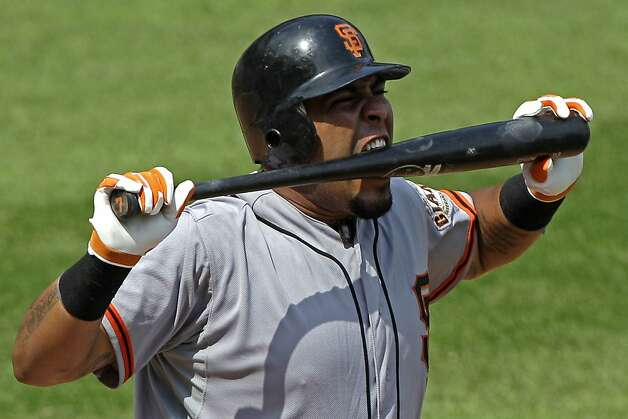San Francisco Giants' Hector Sanchez bites his bat after hitting a foul ball off his foot during an at-bat in the seventh inning of a baseball game against the Pittsburgh Pirates in Pittsburgh, Sunday, July 8, 2012. The Pirates won 13-2. (AP Photo/Gene J. Puskar) Photo: Gene J. Puskar, Associated Press