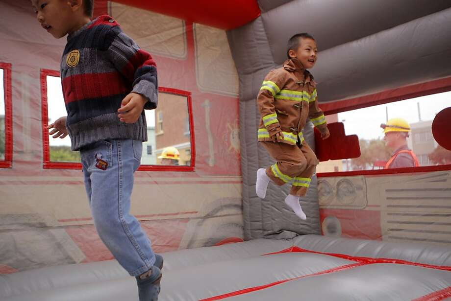 Wesley and Timothy Huang, jump in an inflatable firetruck house on Sunday, July 8, 2012, at the San Francisco Fire Department NERT, (Neighborhood Emergency Response Team), Firefighters Local  798 and Laborfest for free and fun readiness training, on Folsom Street in San Francisco, Calif. Photo: Megan Farmer, The Chronicle