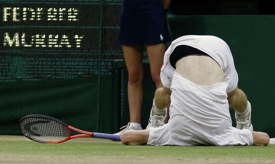 Andy Murray of Britain takes a tumble during the men's singles final match against Roger Federer of