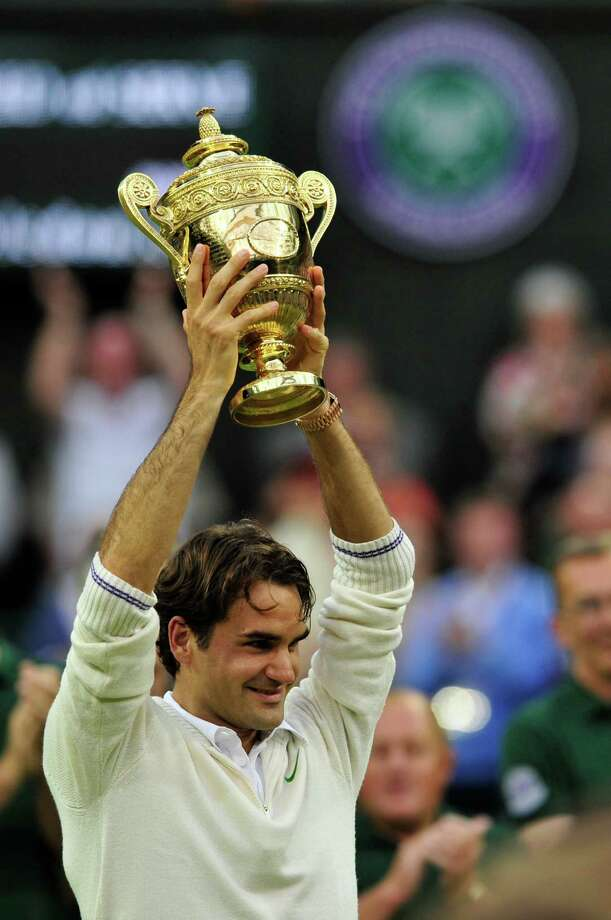 Switzerland's Roger Federer celebrates with the trophy after his men's singles final victory over Britain's Andy Murray on day 13 of the 2012 Wimbledon Championships tennis tournament at the All England Tennis Club in Wimbledon, southwest London, on July 8, 2012. Federer won the match 4-6, 7-5, 6-3, 6-4. AFP PHOTO/ GLYN KIRK      RESTRICTED TO EDITORIAL USEGLYN KIRK/AFP/GettyImages Photo: GLYN KIRK