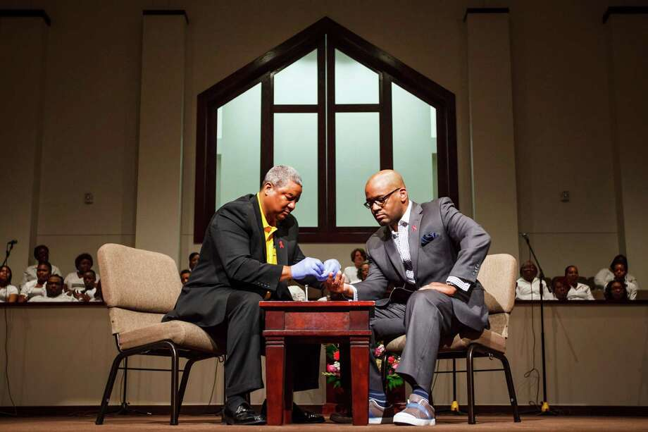 """Norman Mitchell, left, performs an HIV test on the Rev. Timothy Sloan during a service Sunday at St. Luke Missionary Baptist Church in Humble. The NAACP, Bee Busy Wellness Center and Sloan sponsored the """"Day of Unity"""" to talk about HIV/AIDS. Photo: Michael Paulsen / © 2012 Houston Chronicle"""