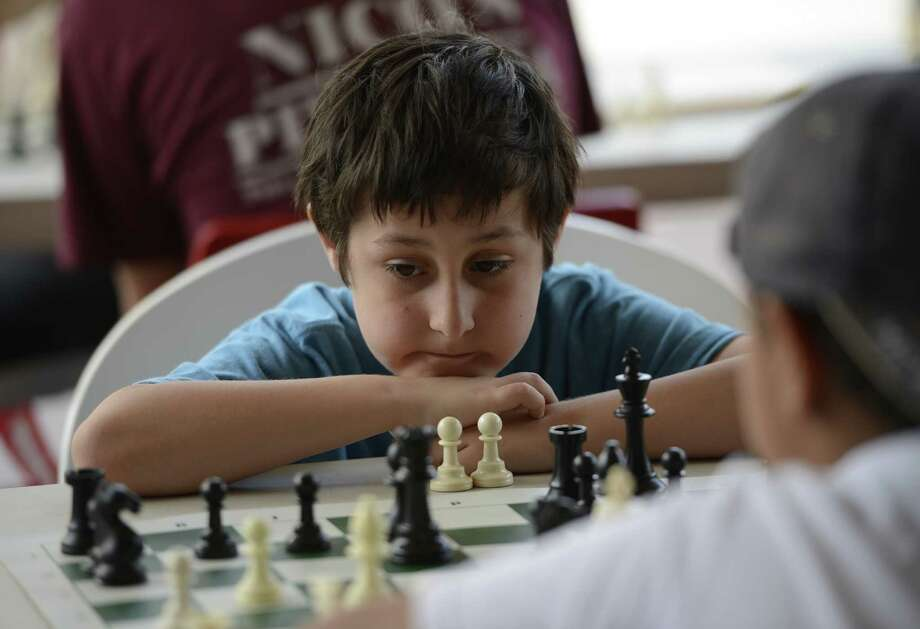 Noah Decker, 9, ponders a chess move at the Schenectady City Mission hosted chess play in front of Proctors Theatre in Schenectady, N.Y. July 2, 2012.    (Skip Dickstein/Times Union) Photo: Skip Dickstein / 00018238A