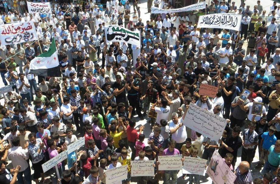 "This citizen journalism image provided by Shaam News Network SNN, taken on Friday, July 6, 2012, purports to show Syrians chanting slogans during a demonstration in Idlib, north Syria. Syria's military began large-scale exercises simulating defense against outside ""aggression,"" the state-run news agency said Sunday an apparent warning to other countries not to intervene in the country's crisis. (AP Photo/Shaam News Network, SNN)THE ASSOCIATED PRESS IS UNABLE TO INDEPENDENTLY VERIFY THE AUTHENTICITY, CONTENT, LOCATION OR DATE OF THIS HANDOUT PHOTO Photo: Anonymous"