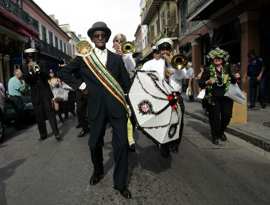 FILE - In this Feb. 17, 2006 file photo, Uncle Lionel Batiste, center with umbrella, dances during the Krew of Cork parade through New Orleans' French Quarter. Batiste, the vocalist, bass drummer and assistant band leader of the Treme Brass Band, has died. He was 81. Band leader Benny Jones Sr. says Batiste died Sunday, July 8, 2012. (AP Photo/Carolyn Kaster, File) Photo: Carolyn Kaster