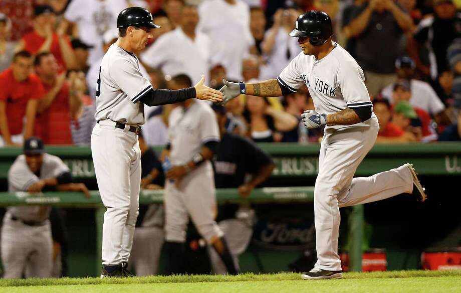 BOSTON, MA - JULY 08:  Andruw Jones #22 of the New York Yankees is congratulated by third base coach Rob Thomson #59 after hitting a two run home run against the Boston Red Sox during the game on July 8, 2012 at Fenway Park in Boston, Massachusetts.  (Photo by Jared Wickerham/Getty Images) Photo: Jared Wickerham