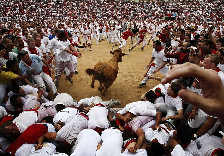 A cow jumps over revelers in a bullring during the second running of the bulls at the San Fermin fiestas, in Pamplona northern Spain, Sunday, July 8, 2012.(AP Photo/Ivan Aguinaga) Photo: Ivan Aguinaga, Associated Press