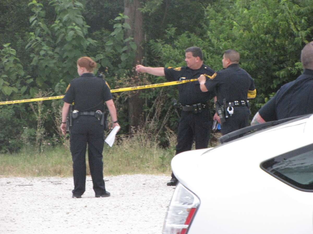 San Antonio police investigate the scene where a woman's nude body was apparently dumped several days ago. Neighbors reported a strong odor Sunday evening, when police found the woman's decomposing body.