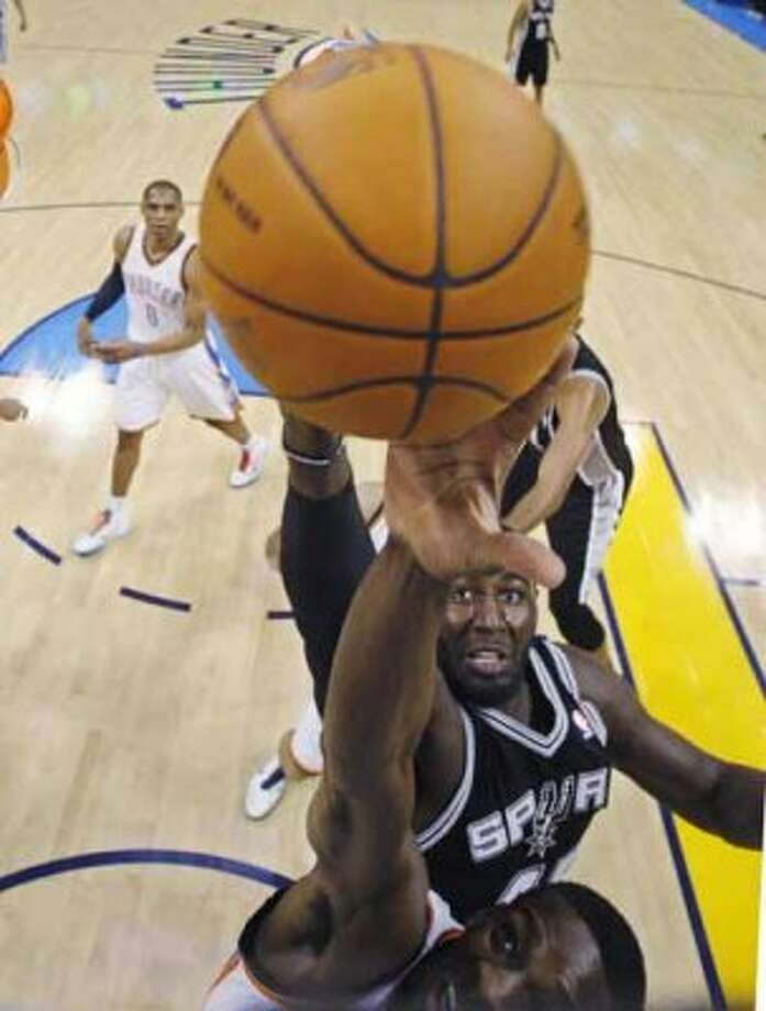 San Antonio Spurs center DeJuan Blair, top, reaches for a rebound with Oklahoma City Thunder forward Jeff Green, bottom, in the first quarter of an NBA basketball game in Oklahoma City, Sunday, Nov. 14, 2010. (AP Photo/Sue Ogrocki) (AP)